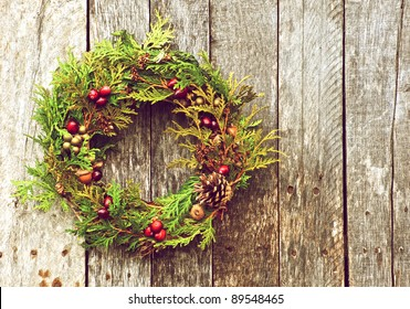 Christmas wreath with natural decorations hanging on a rustic wooden wall with copy space.