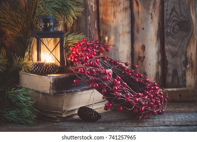 Christmas wreath on books with a lantern on the wooden background. Toned.