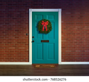 Christmas wreath on bright blue front door with welcome mat.