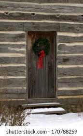 Christmas wreath on the door of an historic log cabin