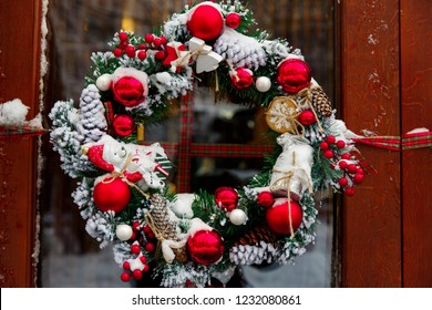 Christmas wreath on a door with red decoration, balls and snow
