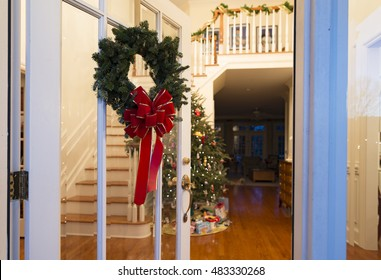 Christmas wreath on a glass front door open to the foyer with a decorated tree