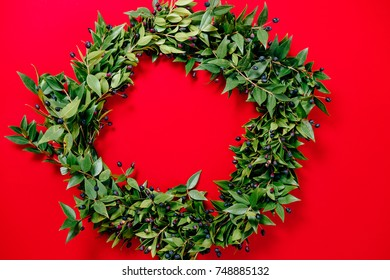 Christmas wreath on red background. Top View