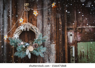 Christmas wreath on rustic wooden door background of blue tree. Christmas new year background for greetings.