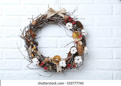 Christmas wreath on white brick wall background