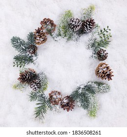 Christmas wreath with pines on white snow
