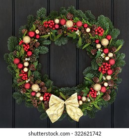 Christmas wreath with red and gold bauble decorations, bow, holly, mistletoe, pine cones and blue spruce fir over dark wood front door background.