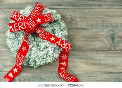 Christmas wreath with red ribbon bow on wooden background. Festive decoration. Merry Christmas! Vintage style toned picture