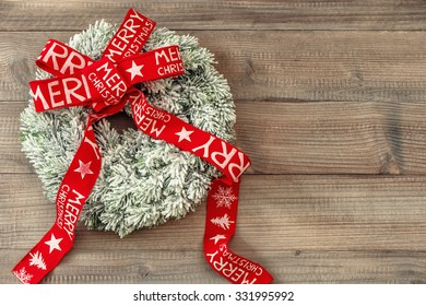 Christmas wreath with red ribbon on wooden background. Festive decoration. Merry Christmas!