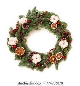 Christmas wreath with red shiny beads with flowers of cotton and slices of dried oranges