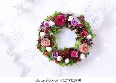 Christmas wreath salad with colorful radish,lettuce,redonion,prosciuutto,grape,and mozzarella on white plate.