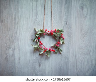 Christmas wreath in a shape of mistletoe with red berries hang on rustic wooden door, traditional Xmas ornament. Minimalist trendy Xmas decor.