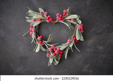 Christmas wreath shaped as decorative heart, made from red mistletoe berries and leaves, on dark textured background