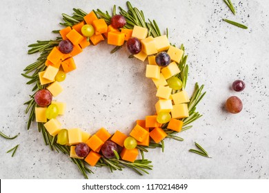 Christmas wreath of snacks made of cheese and grapes. Christmas background concept.