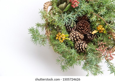 Christmas wreath with wild berries, conifer cones, spruce branches on white background