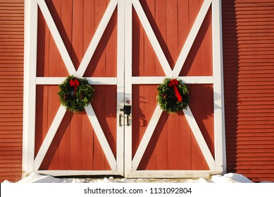Christmas wreaths adorn the red doors of a New England barn