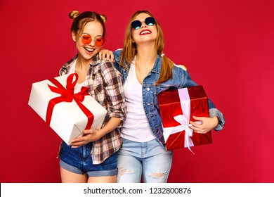Christmas, x-mas, concept.Two smiling beautiful women in stylish clothes.Girls posing on red background.Models with big gift boxes.Having fun,ready for celebration.Bright holiday of best friends
