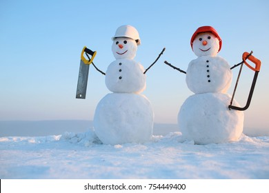 Christmas or xmas decoration. New year snowman from snow with saw. Building and repair work. Happy holiday and celebration. Snowman builder in winter in helmet.