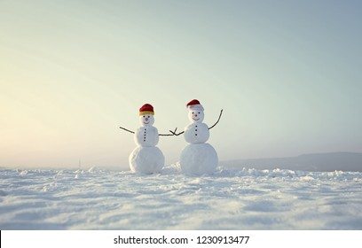Christmas or xmas decoration. Snowman couple outdoor. New year snowmen from snow in santa hat. Happy holiday and celebration. Santa claus hat in winter.