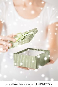 christmas, x-mas, gifts, presents, celebration concept - woman hands opening gift box