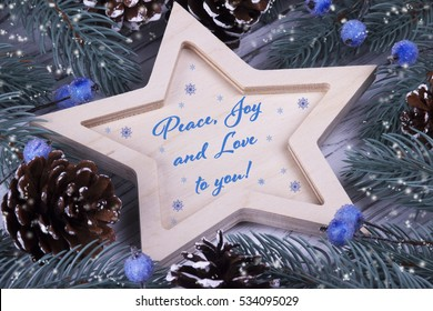 Christmas Xmas New Year Holiday greeting card with wooden five pointed star fir branches cones blue berries and text Peace Love and Joy to you