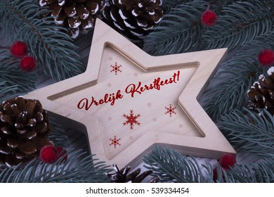 Christmas Xmas New Year Holiday greeting card with wooden five pointed star fir branches cones and text Vrolijk Kerstfeest