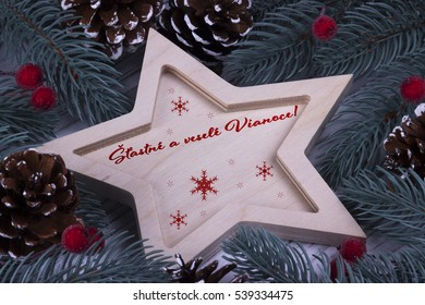 Christmas Xmas New Year Holiday greeting card with wooden five pointed star fir branches cones and text Vianoce
