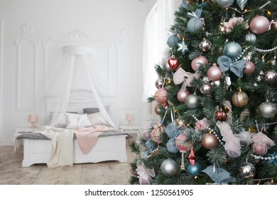 Christmas, xmas, New Year interior with pink and turquoise fur-tree decoration with balls and bowknots, ribbons, white wall and pastel color bed on background, shallow doff