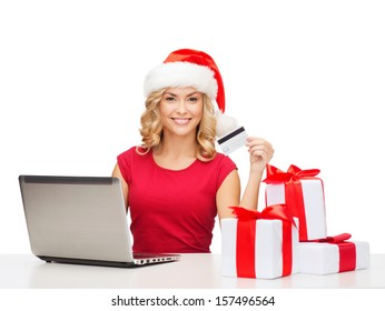 christmas, x-mas, online shopping concept - woman in santa helper hat with gift boxes, laptop computer and credit card