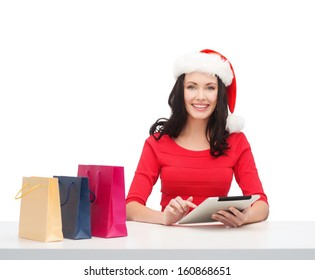 christmas, x-mas, online shopping concept - woman in santa helper hat with gift box and tablet pc computer