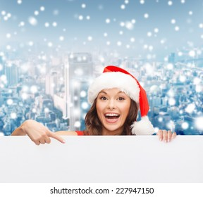 christmas, x-mas, people, advertisement and sale concept - happy woman in santa helper hat with blank white board over snowy city background