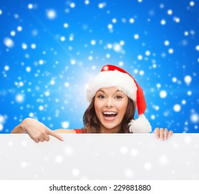 christmas, x-mas, people, advertisement and sale concept - happy woman in santa helper hat with blank white board over blue snowy background