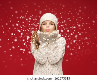 christmas, x-mas, people, happiness concept - happy girl in winter clothes blowing on palms