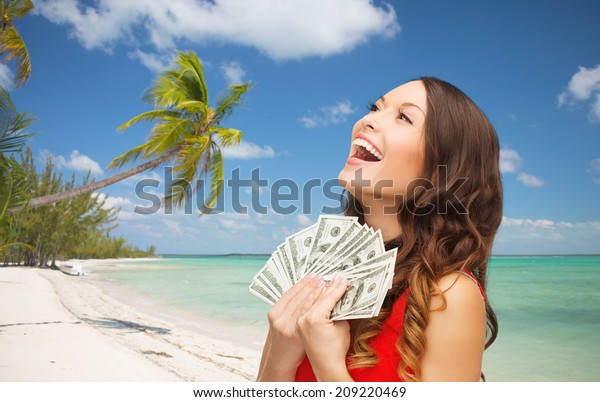 christmas, x-mas, sale, banking and travel concept - smiling woman in red dress with us dollar money over tropical beach background