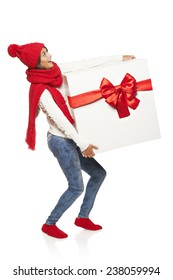 Christmas, x-mas, winter gift concept. Full length surprised excited woman in winter clothing carrying huge heavy gift box with red bow,  looking up at blank copy space, isolated on white