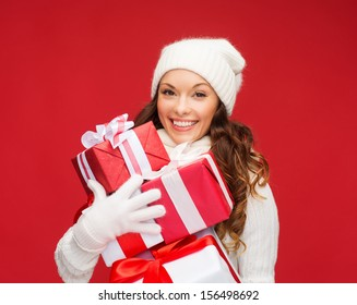 christmas, x-mas, winter, happiness concept - smiling woman in sweater and hat with many gift boxes