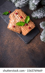 Christmas yule log cake. Traditional chocolate dessert on festive background