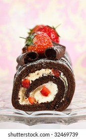 Christmas yule log decorated with chocolate curls and strawberries on glass comport