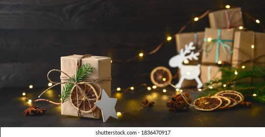 Christmas zero waste concept. Eco friendly packaging gifts in kraft paper on a dark wooden table. DIY gifts, eco decor. Copy space, banner.