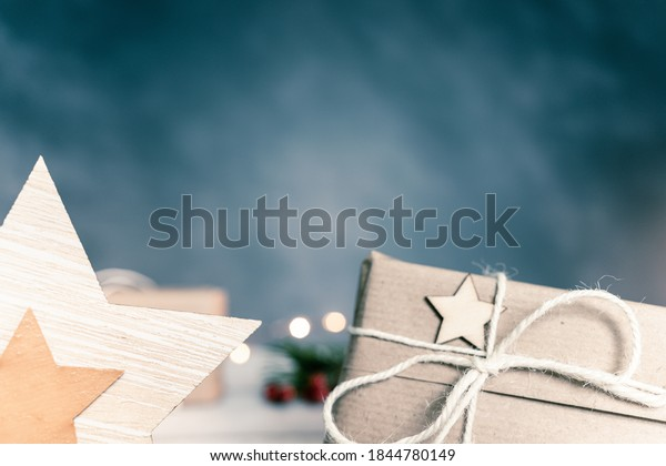 Christmas and zero waste, eco friendly packaging. wrapped gifts in craft paper with wooden snowflakes and star on a wooden table on a dark background. ecological Christmas holiday concept, eco decor