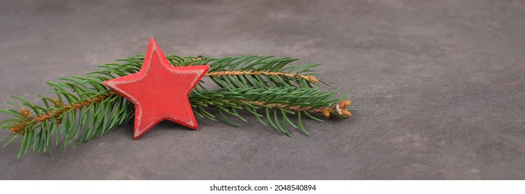 Christmasbackground with a branch of fir and a red colored star