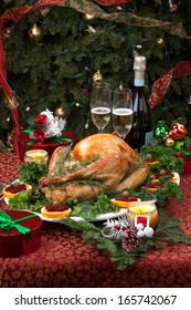 Christmas-decorated table with feast, gifts, roasted turkey, candles, champagne, and Christmas tree on back.