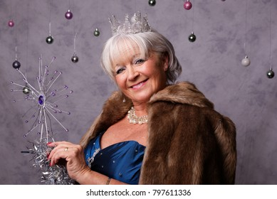 Christmas/party theme. Mature, white female wearing a party dress, fur cape and tiara against a grey background