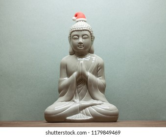Christmass Buddha in red santa hat on blue background