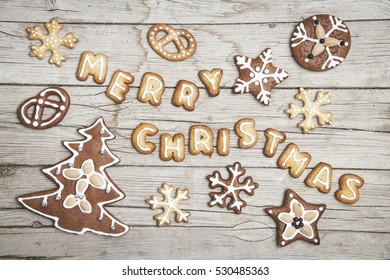 Christmassy grey wood background with gingerbread and Merry Christma's letter