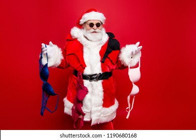Christmastime December noel wish winter sale discount black Friday. Grandfather stylish aged mature Santa in tradition costume headwear white beard hold bra isolated on red background