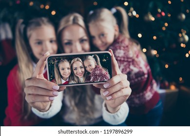 Christmastime December winter noel festive eve. Focus on smartphone screen blurred background blonde parent mama with two small little preteen in sweater in comfort cosy home house make self picture
