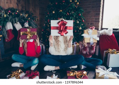 Christmastime winter festive event! Full legs body size funny funky playful blonde wife and two little pre-teen offspring in shoes sweater hold big package front of face sit on floor in comfort house