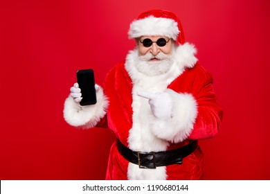 Christmastime winter wish December sale discount. Aged grandfather trendy Santa in tradition costume headwear white beard pointer finger on gadget device propose solution isolated on red background