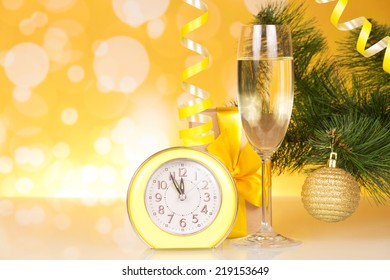 Christmas-tree branch, glass of champagne, gift box and about twelve hours
